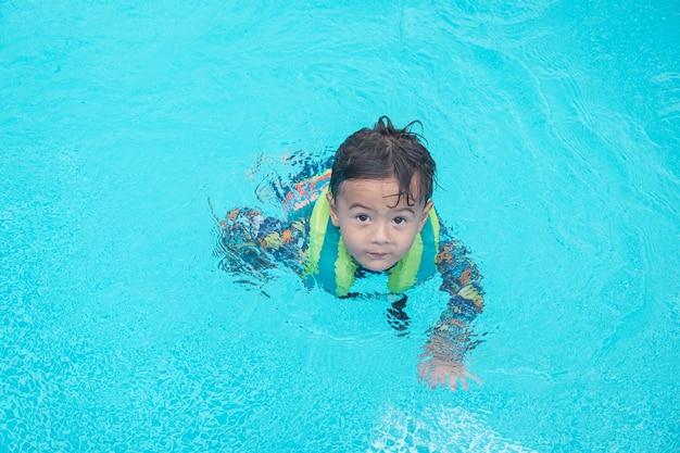 Menino feliz nadar e mergulhar na água, peito de criança com diversão na piscina. estilo de vida ativo e saudável, esportes aquáticos e aulas com os pais nas férias de verão com a criança.