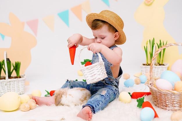 Menino feliz no chapéu alimenta coelhinha fofa