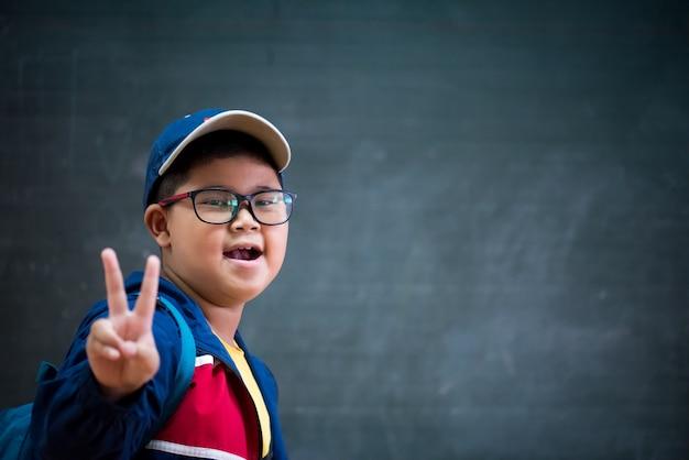 Menino feliz nos vidros que mostram dois dedos para de volta ao conceito da escola.