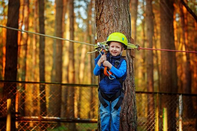 Menino feliz pequeno da criança no parque da aventura no equipamento de segurança no dia de verão.