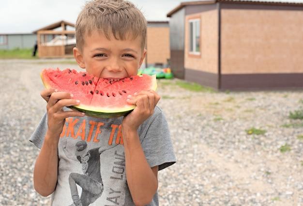 Menino feliz que come uma melancia madura.