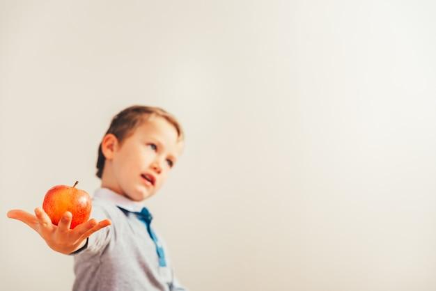 Menino feliz que mostra seu almoço, uma maçã que realiza em sua mão, fruta saudável para crescer.