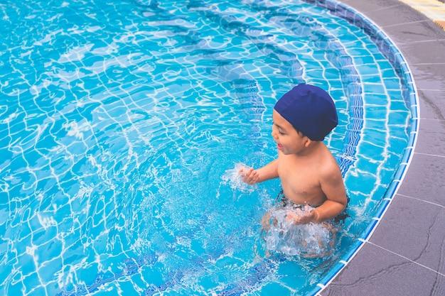 Menino feliz que senta-se em torno da piscina e que olha sua irmã.
