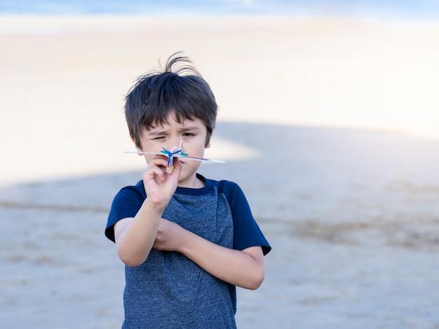 Menino feliz retrato brincando com o avião de brinquedo contra o fundo da praia de areia embaçada