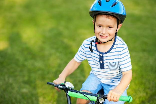 Menino feliz se divertindo andando de bicicleta