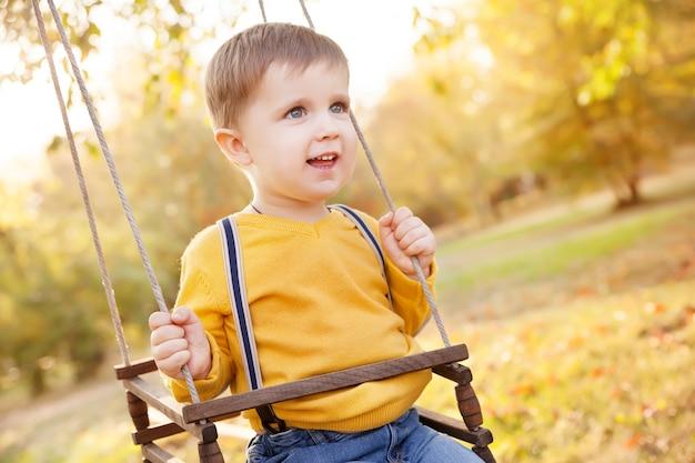 Menino feliz, se divertindo em um passeio de balanço em um jardim, um dia de outono