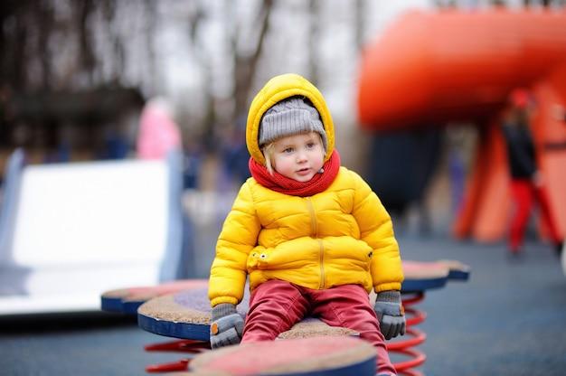 Menino feliz se divertindo no playground ao ar livre. primavera e outono lazer ativo para as crianças.