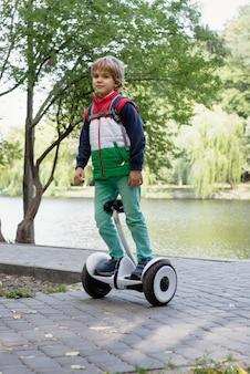 Menino feliz se equilibrando em uma prancha elétrica no parque ensolarado