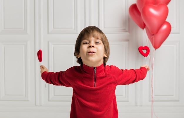 Menino feliz segurando dois corações em fundo branco com corações de balões