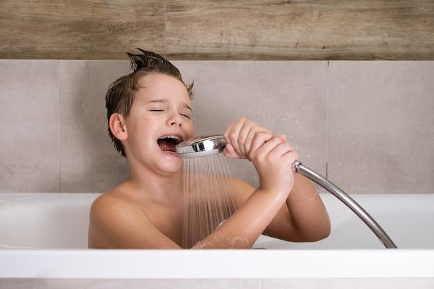 Menino feliz segurando o chuveiro e cantando enquanto se lava no banheiro criança toma banho em casa infância saudável