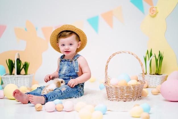 Menino feliz, segurando o coelhinho fofo perto de ovos de páscoa pintados