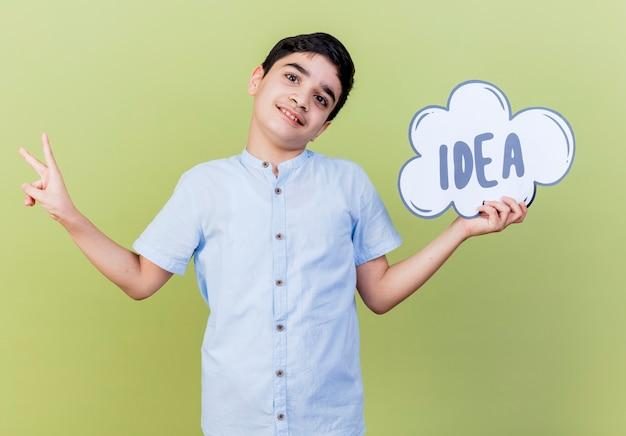 Menino feliz segurando uma bolha de ideia, olhando para a frente, fazendo o sinal da paz, isolado na parede verde oliva
