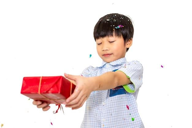 Menino feliz segurando uma caixa de presente em fundo branco.