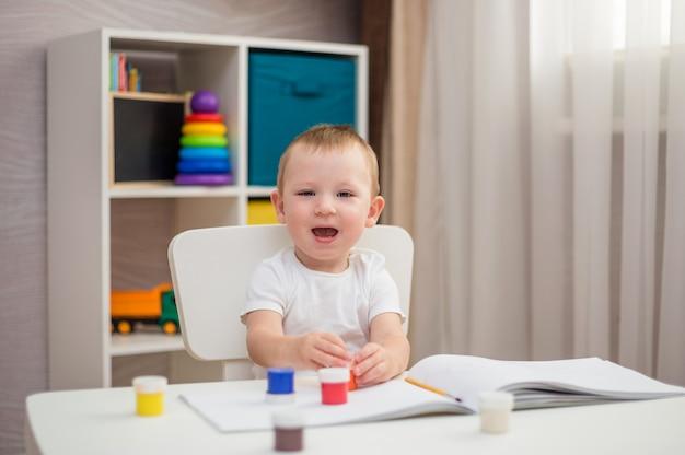Menino feliz sentado a uma mesa com tintas e pincéis
