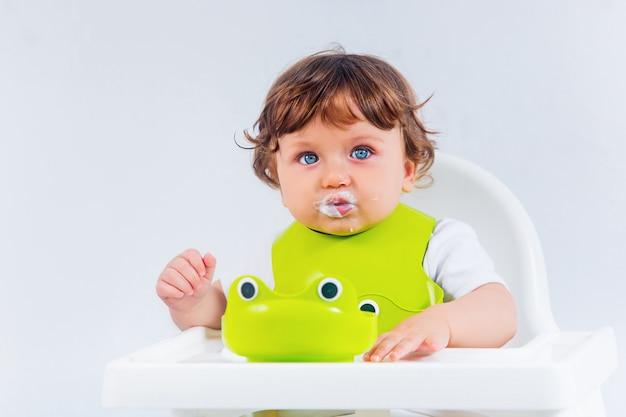 Menino feliz sentado e comendo