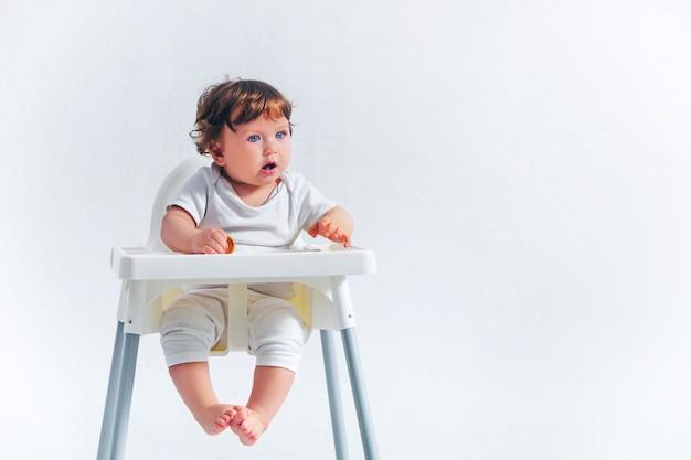 Menino feliz, sentado na cadeira de bebê