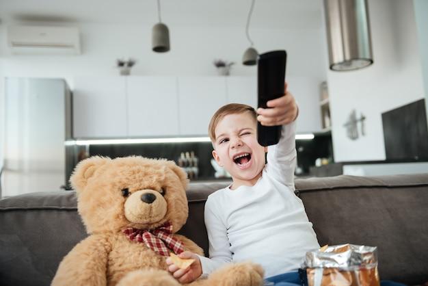Menino feliz sentado no sofá com o ursinho de pelúcia em casa e assistindo tv enquanto come batatas fritas. segurando o controle remoto.