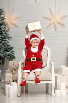 Menino feliz sorrindo em traje de papai noel, sentado na poltrona perto de árvore de natal e segurando a caixa de presente de natal