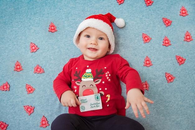 Menino feliz sorrindo entre árvores de natal festivas de natal