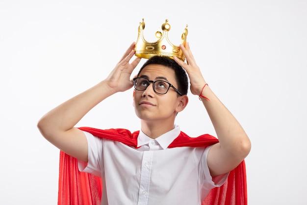 Menino feliz super-herói com capa vermelha usando óculos, segurando a coroa acima da cabeça, olhando para cima, isolado no fundo branco