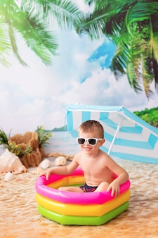 Menino feliz tomando banho em uma piscina inflável brilhante