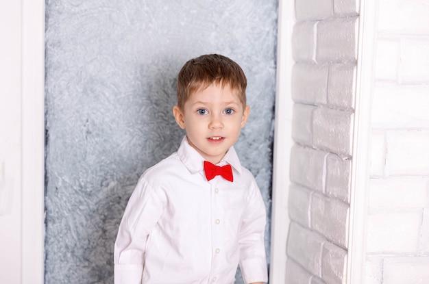 Menino feliz vestindo uma camisa e uma gravata borboleta vermelha