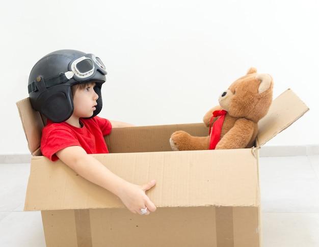 Menino feliz voando em uma caixa e usando um chapéu com seu brinquedo