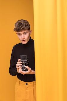 Menino filmando com uma filmadora em uma cena amarela Foto gratuita