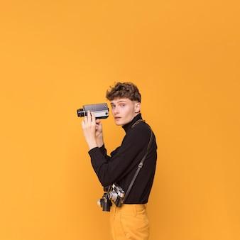 Menino filmando com uma filmadora em uma cena amarela
