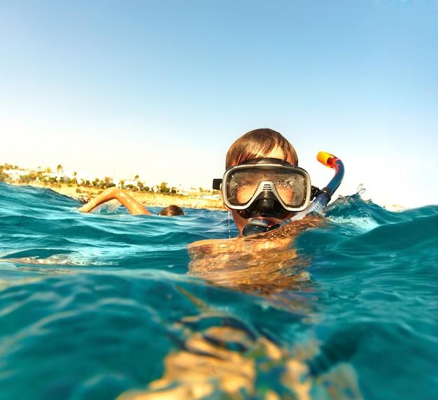 Menino flutua no mar, férias de verão
