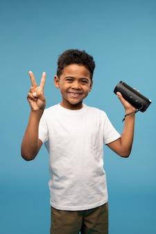 Menino fofo alegre de origem africana mostrando um gesto de paz enquanto se diverte e ouve música na coluna smart wireless
