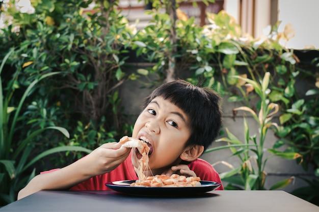 Menino fofo asiático com camisa vermelha sentado feliz comendo pizza com plantas no fundo