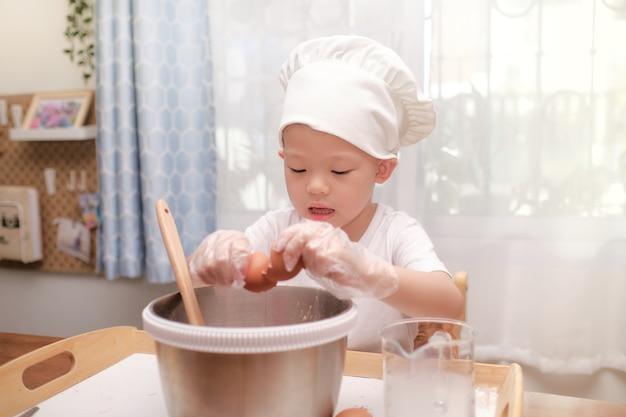 Menino fofo asiático de 4 anos se divertindo preparando bolo ou panquecas, quebrando um ovo em casa