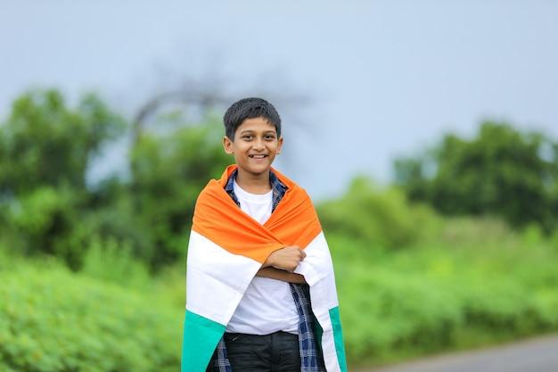 Menino fofo com a bandeira tricolor nacional indiana