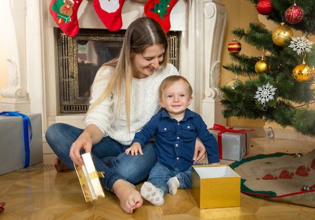 Menino fofo com a mãe abrindo caixas de presente debaixo da árvore de natal na sala de estar