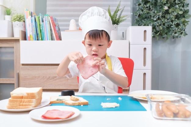 Menino fofo com chapéu de chef e avental preparando sanduíches