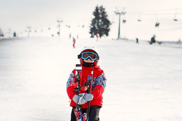 Menino fofo com esquis e roupa de esqui