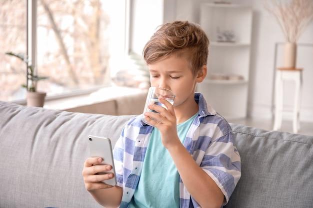 Menino fofo com o celular bebendo água em casa