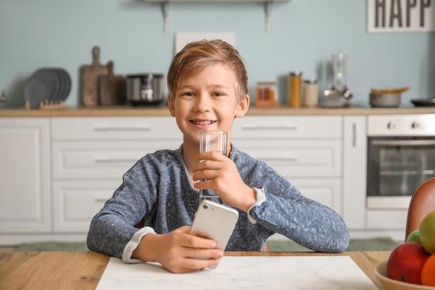 Menino fofo com um celular bebendo água na cozinha