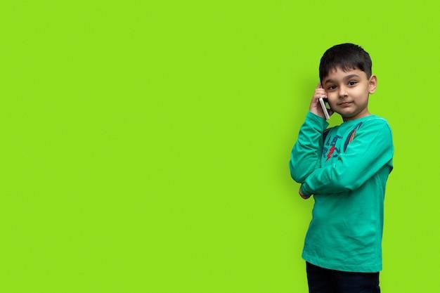 Menino fofo com uma camisa verde falando ao telefone em um fundo simples com espaço de cópia