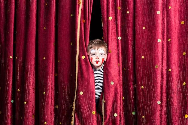 Menino fofo com uma pintura facial vermelha colorida e uma fantasia espiando por entre as cortinas do palco enquanto espera o início da pantomima