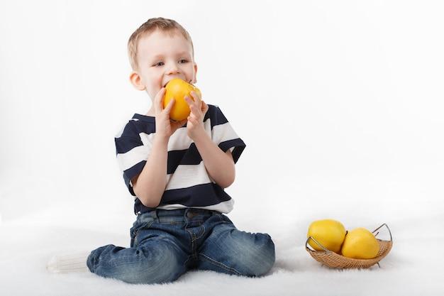 Menino fofo comendo uma maçã amarela e sorrindo em branco