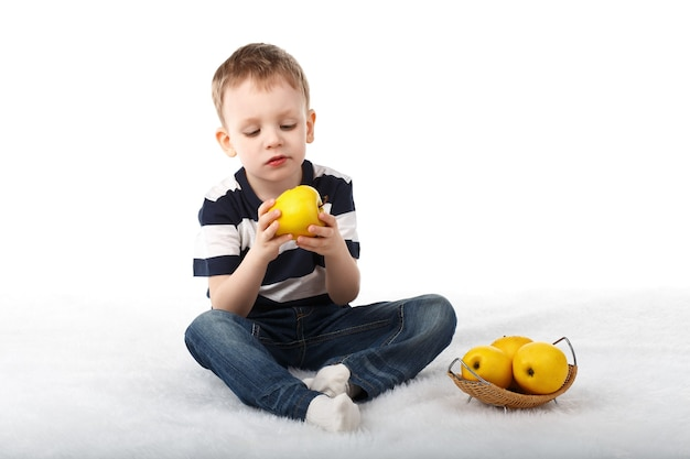Menino fofo comendo uma maçã amarela e sorrindo, isolado no branco