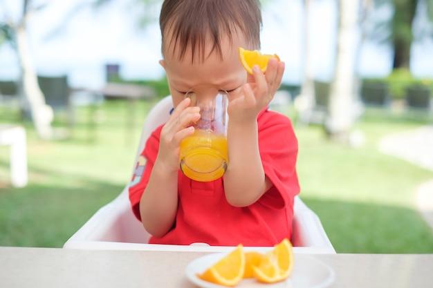 Menino fofo criança asiática sentada em uma cadeira alta segurando e bebendo uma bebida gelada de suco de laranja saboroso em um copo durante o café da manhã