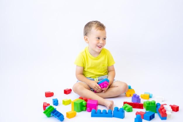 Menino fofo, criança brinca com um construtor, constrói sobre um fundo branco, isolado
