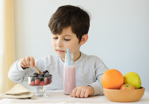 Menino fofo criança comendo frutas, iogurte dentro de casa, comida infantil, comida saudável para crianças