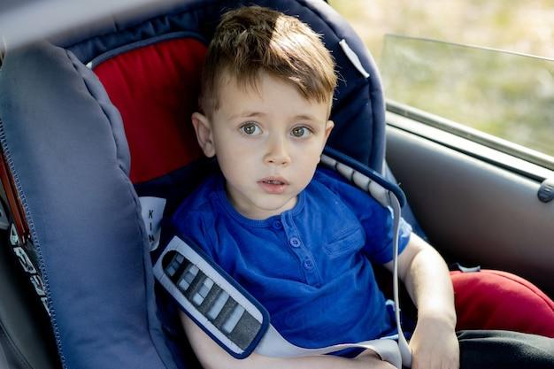 Menino fofo de 3 a 4 anos de idade pré-escolar sentado na cadeirinha do carro chorando durante a viagem da família de carro