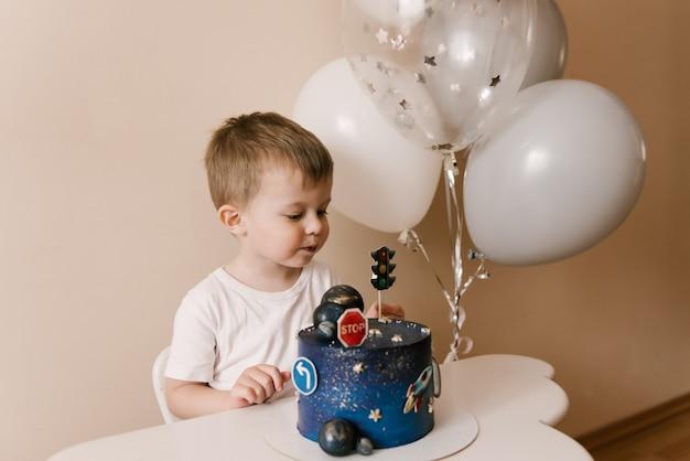 Menino fofo de 3 anos está comemorando seu aniversário e comendo um lindo bolo delicioso, foto de uma criança com balões