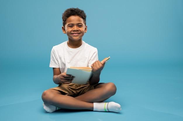 Menino fofo de escola de etnia africana segurando um livro aberto perto do rosto e espiando pela capa enquanto está sentado no chão