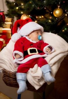 Menino fofo de natal dormindo em uma cesta na sala de estar